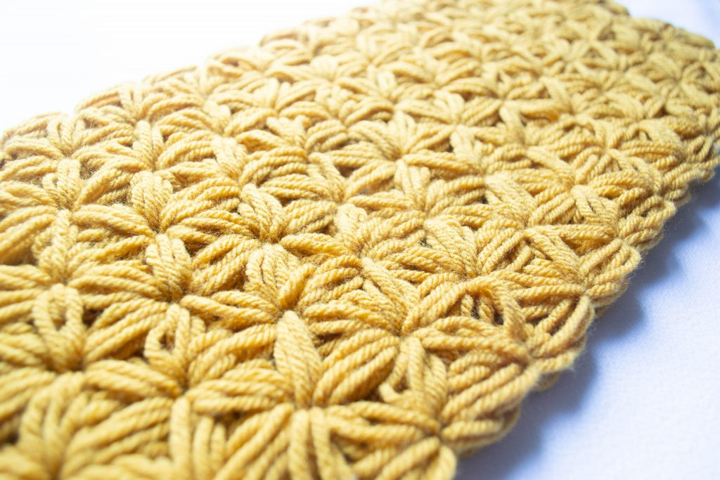 A starburst crochet stitch in a yellow beanie