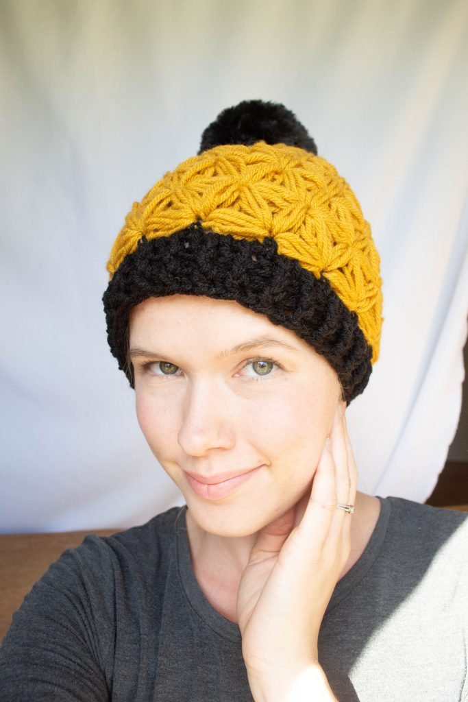 model wearing a yellow crochet beanie