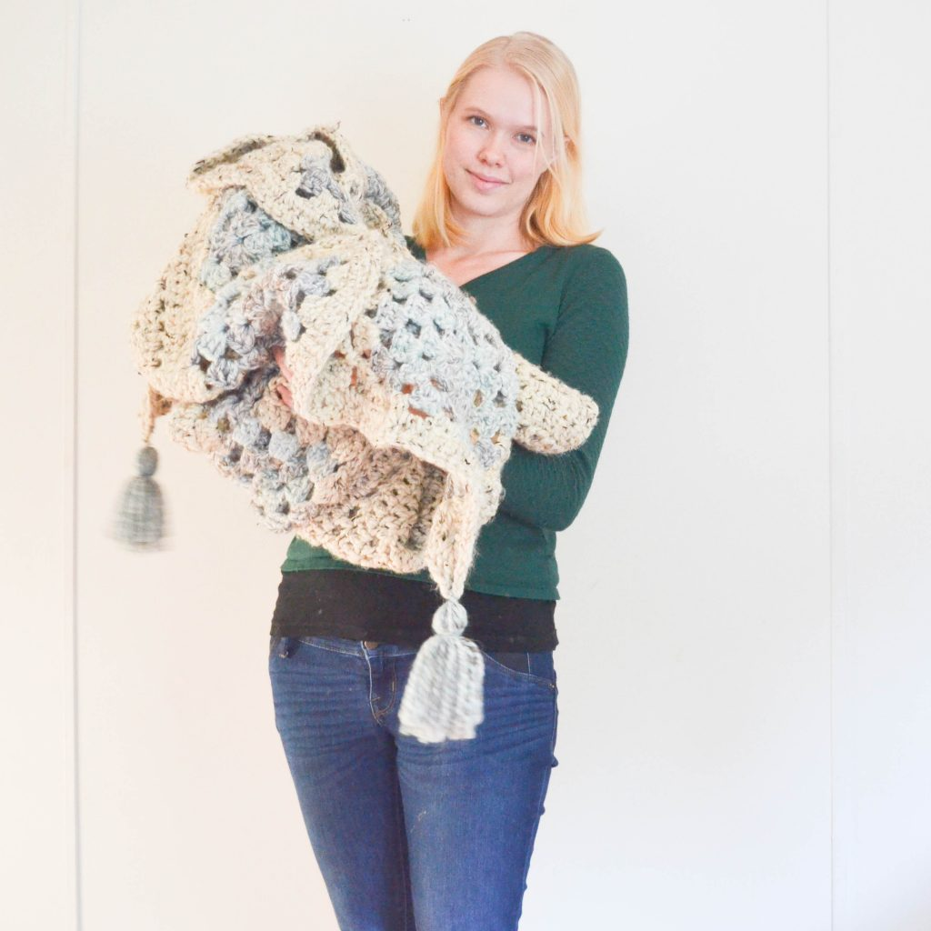 Amelia holding this crochet blanket and showing off the design and tassel details