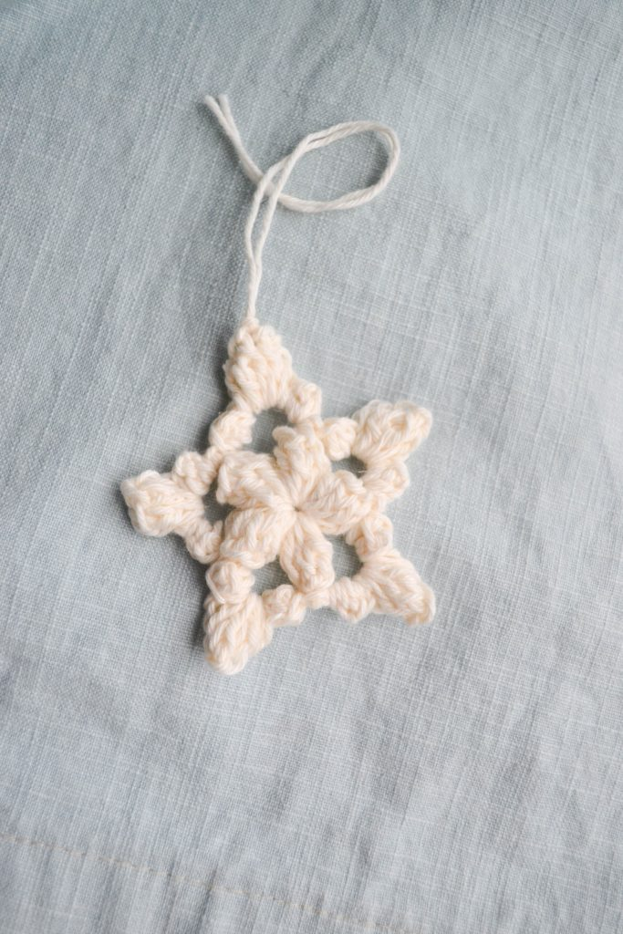 white crochet star ornament on a light blue background.